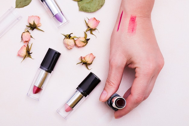 Vue élevée, main féminine, tenue, rouges lèvres, à, rose séchée, bourgeons, sur, toile de fond blanc