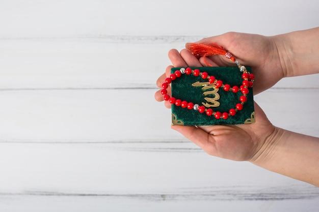Vue élevée, de, main homme, tenue, livre kuran vert, et, perles prière rouge, contre, bureau blanc
