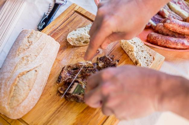 Vue élevée d'une main humaine tranchage de la viande cuite sur une planche à découper en bois
