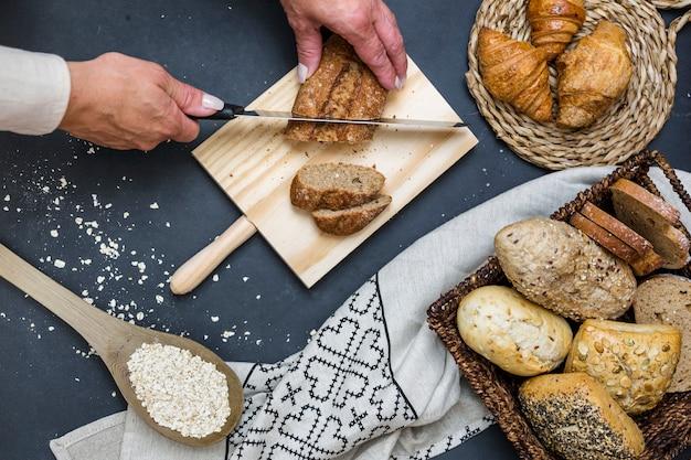 Vue élevée de la main d'une personne en tranches de pain avec un couteau
