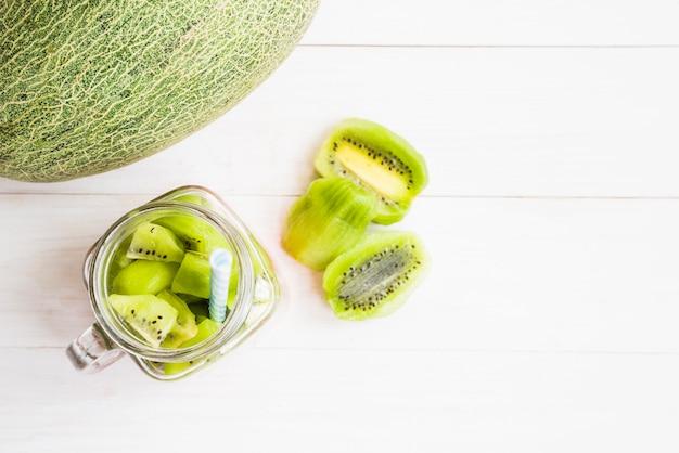 Vue élevée, de, melon, fruit, près, kiwi, tranches, dans, pot, sur, toile toile de fond