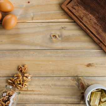 Vue élevée de noix; morceaux de chocolat et oeufs bruns sur fond en bois