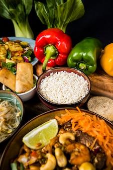 Une vue élevée de nouilles avec du riz; rouleaux de printemps et poivrons