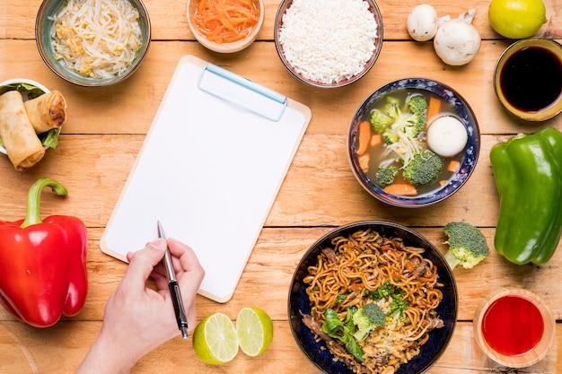 Une vue élevée de la nourriture thaïlandaise avec une personne écrivant sur le presse-papiers avec un stylo
