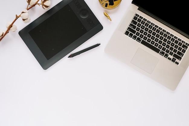 Vue élevée de l'ordinateur portable; tablette numérique graphique et brindille de coton sur fond blanc