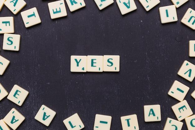 Vue élevée de oui mot fait à partir de lettres scrabble jeu
