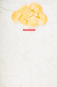 Vue élevée des pâtes mezzalune sur marbre