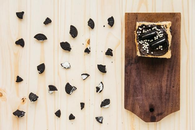 Vue élevée de la pâtisserie près de morceaux de biscuits sur fond en bois