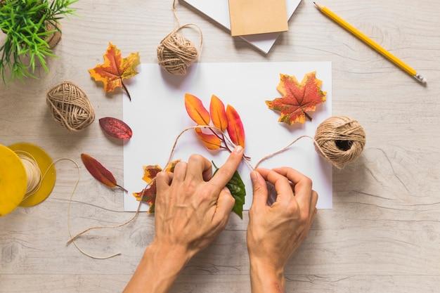 Vue élevée d'une personne attachant les fausses feuilles d'automne avec de la ficelle