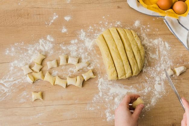 Une vue élevée d'une personne préparant les gnocchi de pâtes italiennes faites maison