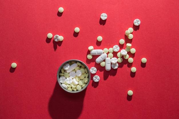 Vue élevée, de, pilules, dans, récipient, sur, arrière-plan rouge