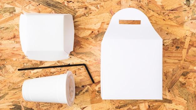 Une vue élevée de plats à emporter blancs sur fond en bois