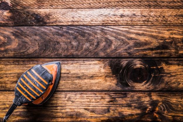Vue élevée de la ponceuse sur fond en bois