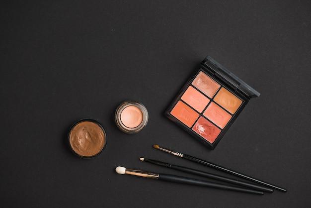 Vue élevée des produits de maquillage et des brosses sur la surface noire