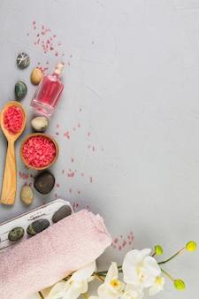 Vue élevée de serviette; pierres de spa; sel; fleurs et huile sur fond gris