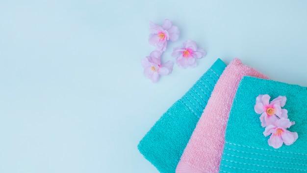 Vue élevée des serviettes; avec des fleurs violettes sur fond bleu