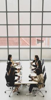 Vue élevée de six femmes d'affaires exécutives assises sur chaque chaise à l'aide d'ordinateurs portables et de tablettes sur une table de conférence en bois dans la salle de réunion du bureau. concept pour réunion d'affaires.