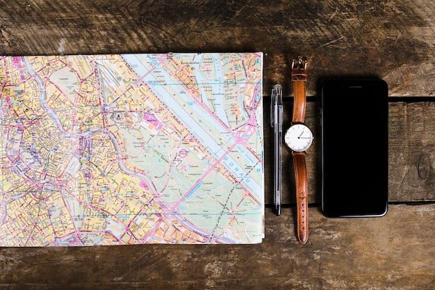 Vue élevée de smartphone, stylo, montre-bracelet, carte sur fond en bois