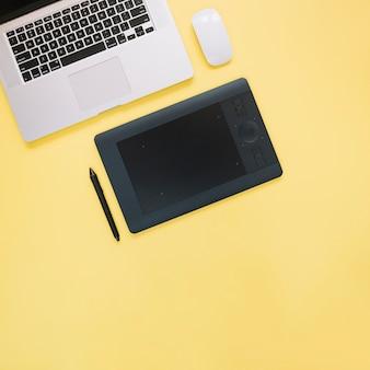 Vue élevée de tablette numérique graphique et ordinateur portable sur fond jaune