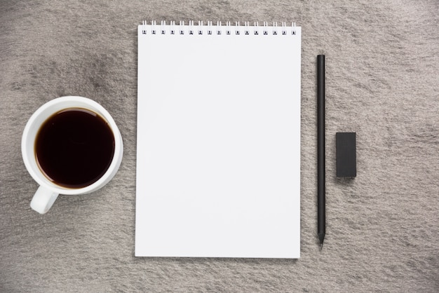 Une vue élevée de la tasse de café; bloc-notes à spirale vierge avec une gomme à effacer noire et un crayon sur un bureau gris