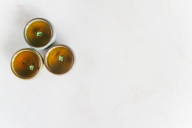 Une vue élevée de tasses à thé à base de plantes sur fond blanc