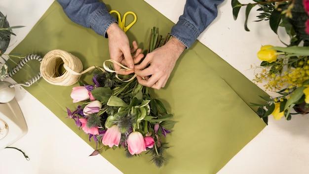 Une vue élevée d'un touriste attachant le bouquet de fleurs avec de la ficelle sur du papier vert sur le bureau