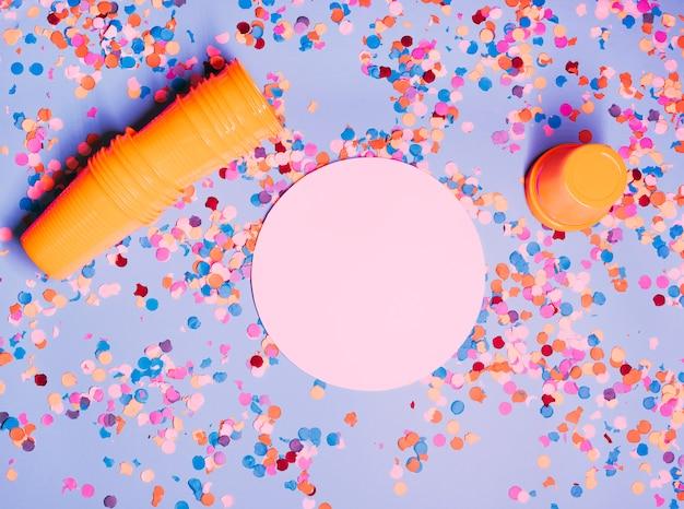 Vue élevée de verres en plastique orange; papier de forme circulaire rose et confettis colorés sur fond bleu