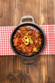 Vue éloignée du dessus du repas de légumes cuits, y compris les légumes et la viande à l'intérieur sur un bureau brun en bois
