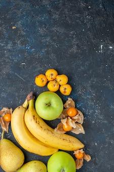Vue éloignée du haut de la banane jaune paire de baies avec des pommes vertes poires sur bleu foncé, baies de fruits frais santé vitamine sweet