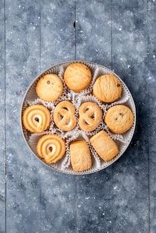 Vue éloignée du haut de délicieux biscuits sucrés différents formés à l'intérieur de l'emballage rond sur un bureau gris, biscuit biscuit gâteau sucré au sucre