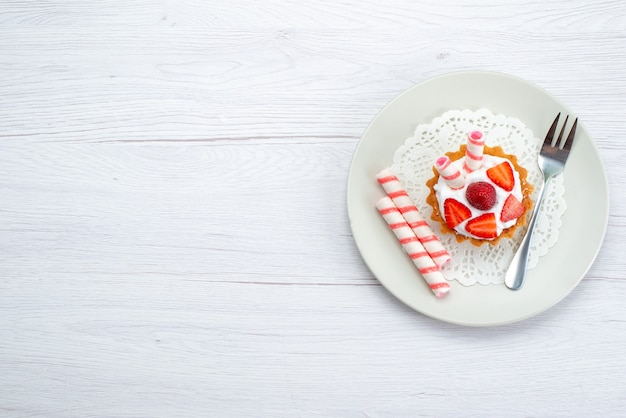 Vue éloignée du haut du petit gâteau à la crème et aux fraises en tranches à l'intérieur de la plaque sur blanc, gâteau aux fruits berry sucre sucré