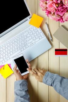 Vue d'ensemble, concept de bureau d'affaires, personne d'affaires utilisant des téléphones mobiles avec carte d'ordinateur portable et de crédit, ordinateur portable, fleur sur bureau.