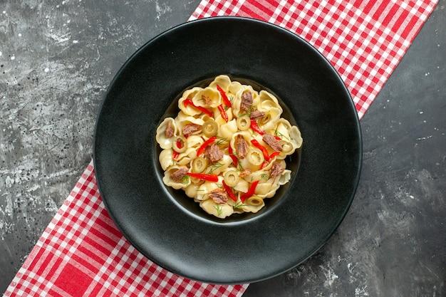 Vue d'ensemble de délicieuses conchiglie au poivre sur une assiette noire et un couteau sur une serviette dénudée rouge sur fond gris