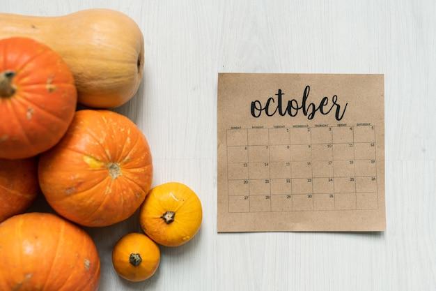 Vue d'ensemble de la feuille de calendrier d'octobre et groupe de citrouilles mûres orange et jaune sur blanc