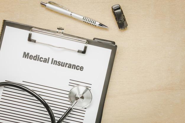 Vue d'ensemble, formulaire d'assurance médicale avec un stéthoscope, une voiture sur fond en bois.
