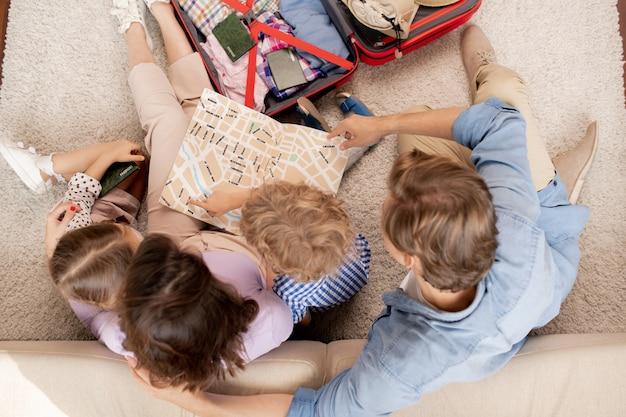 Vue d'ensemble de la jeune famille de parents, de leur fils et de leur fille regardant le guide de la carte tout en partant en voyage ou en camping