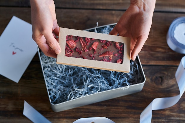 Vue d'ensemble des mains humaines tenant un récipient plat avec cadre transparent tout en le mettant dans une boîte cadeau