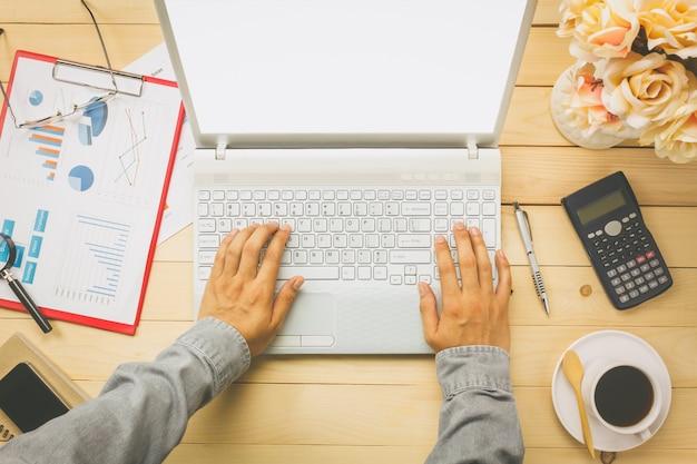 Vue d'ensemble, personne d'affaires qui discute des graphiques et des graphiques avec un ordinateur portable, également un cahier, un café noir, une fleur, un papier fixe, un stylo, une calculatrice sur fond de bureau.
