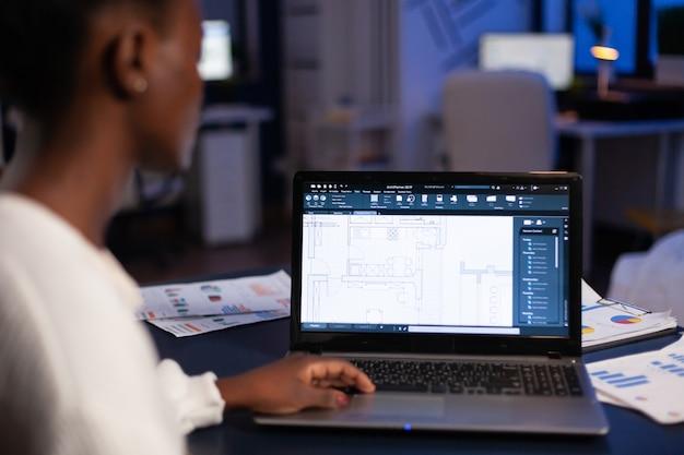 Vue sur l'épaule d'un architecte africain travaillant tard dans la nuit au bureau à l'aide d'un logiciel de cao, impressions bleues