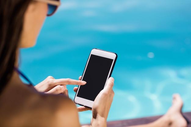 Vue sur l'épaule de brune à l'aide de smartphone au bord de la piscine