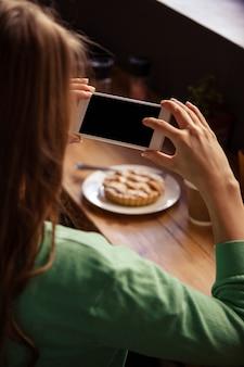 Vue de l'épaule de la femme hipster prenant une photo de pâtisserie