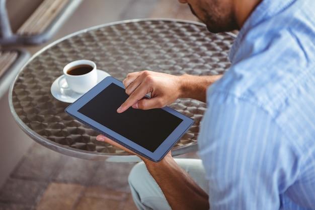 Vue épaule d'homme d'affaires attentif à l'aide d'une tablette à l'extérieur du café