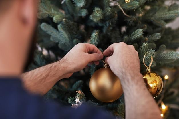 Vue d'épaule d'un homme suspendu à une boule de noël dorée sur un arbre tout en se préparant à la célébration