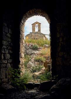 Vue d'un ermitage au sommet de la montagne depuis une fenêtre naturelle