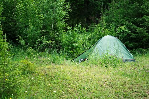 Vue sur un étang vert rond naturel avec une tente de camping verte entourée d'arbres