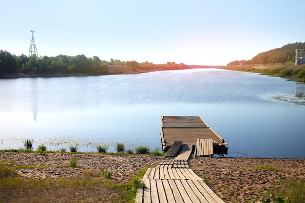 Vue d'été ensoleillée de brige en bois et rivière
