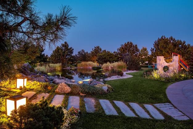 Vue d'été en soirée sur le parc avec étang aire de jeux pour enfants parterres de fleurs et sentiers pavés