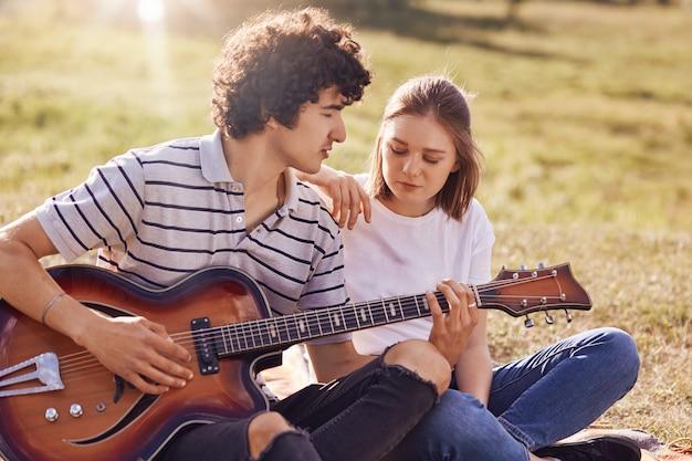 Vue extérieure de la belle femme et son compagnon ont des loisirs, beau adolescent joue de la guitare, regarde avec amour sa petite amie