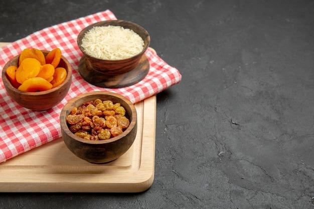 Vue de face d'abricots secs aux raisins secs et de riz sur une surface grise aux raisins secs aux fruits