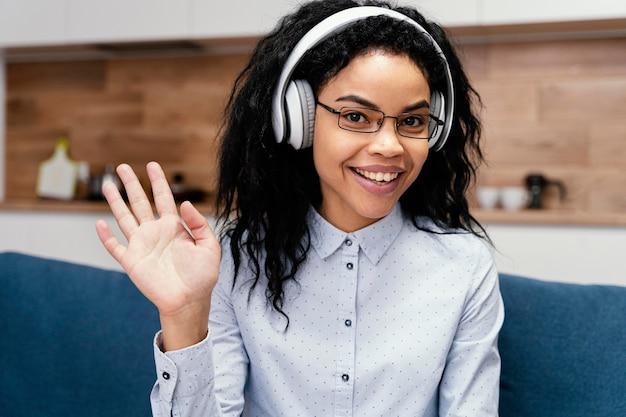 Vue de face d'une adolescente avec des écouteurs pendant l'école en ligne